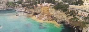 Un costone a picco sul mare che frana e centinaia di bare che galleggiano in acqua
